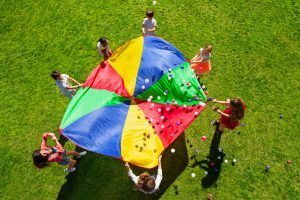 Top view picture of kids standing in a circle on the green lawn and holding rainbow parachute full of colorful balls