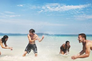 Diverse group of friends playing in the beach water