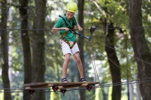 Young cute child boy in summer clothing, safety harness and helmet attached with carbine to cable moves slowly along rope way on green trees sunny bokeh background. Sport, game, leisure concept.